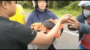 FOTO : Seorang warga saat mengevakuasi bayi malang dari semak.